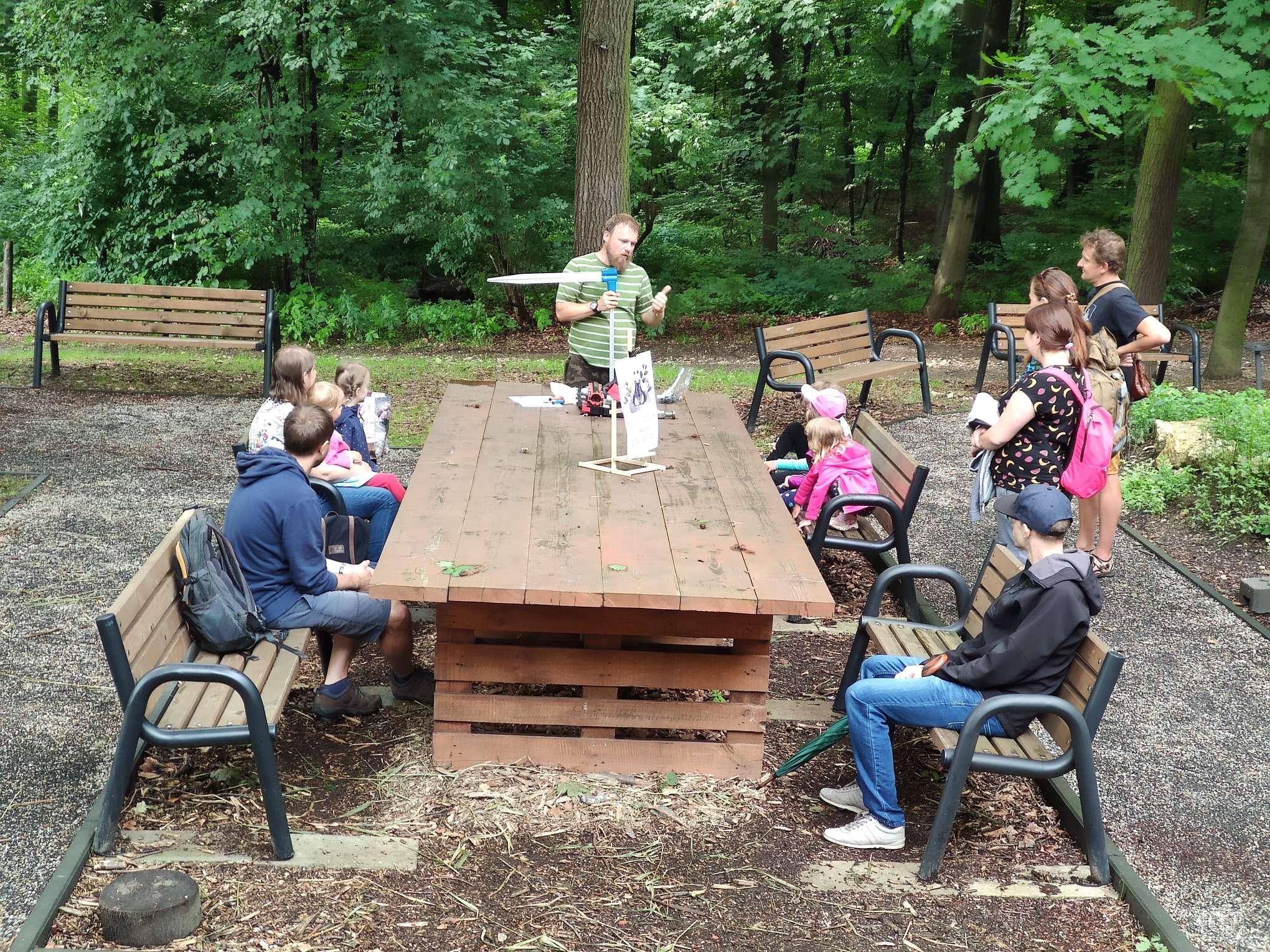 Zdjęcie przedstawiające grupę ludzi z edukatorem na spacerze leśnym w Lesie Wolskim, na pierwszym planie drewniany stół warsztatowy