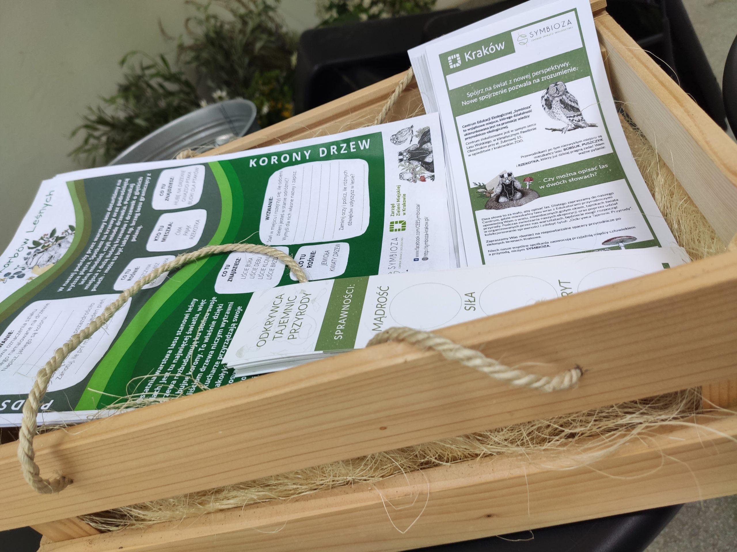 Zdjęcie przedstawiające ulotki i gry terenowe CEE Symbioza w drewnianym koszyku