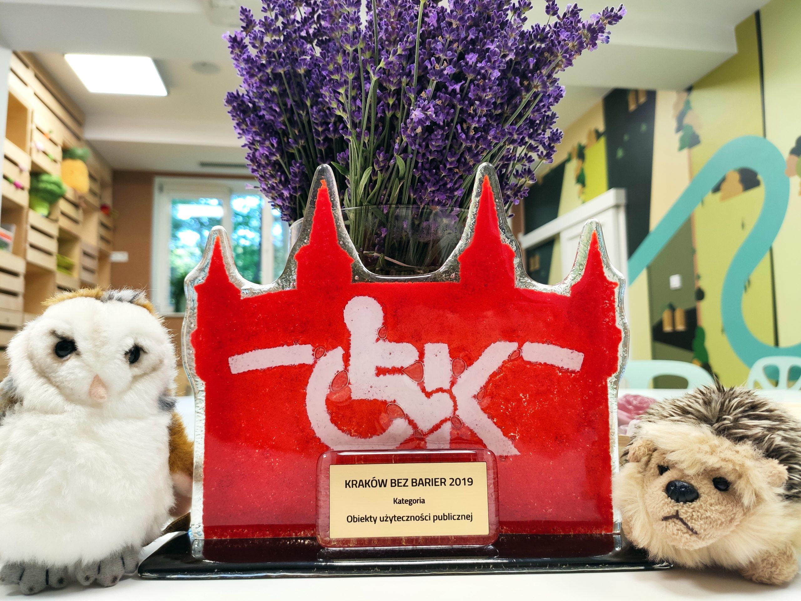 Zdjęcie przedstawiające nagrodę Kraków bez Barier 2019 - obiekty użyteczności publicznej z pluszową sową i jeżem po obu stronach