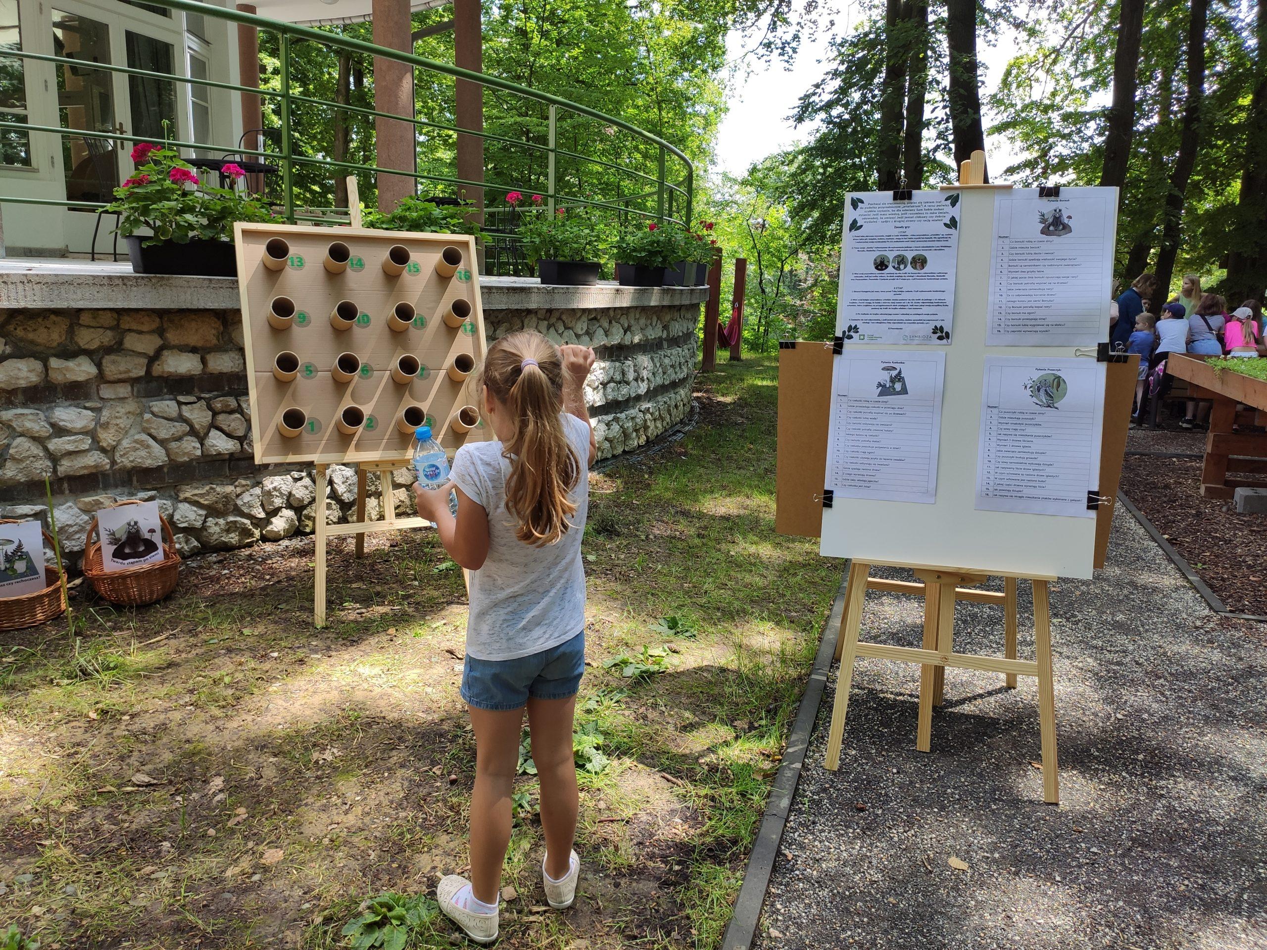 Zdjęcie przedstawiające dziewczynkę grającą w grę terenową leśny dart - rzuca kamieniem do obręczy przed budynkiem CEE Symbioza