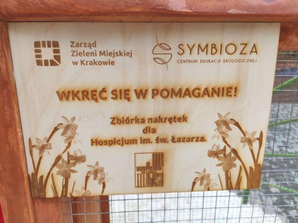 Zdjęcie przedstawiające drewnianą tablicę z napisem wkręć się w pomaganie - zbiórka nakrętek dla Hospicjum im. św. Łazarza - akcja charytatywna CEE Symbioza