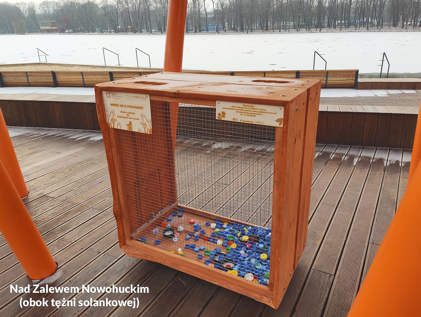 Zdjęcie przedstawiające drewnianą skrzynię na plastikowe nakrętki w nad Zalewem Nowohuckim - akcja charytatywna CEE Symbioza