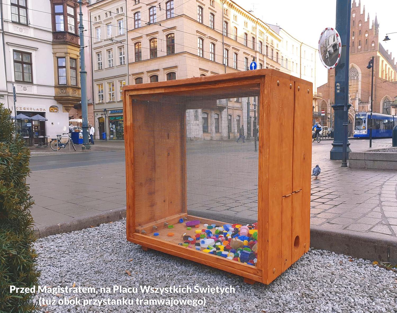 Zdjęcie przedstawiające drewnianą skrzynię na plastikowe nakrętki w przed Magistratem, na Placu Wszystkich Świętych - akcja charytatywna CEE Symbioza