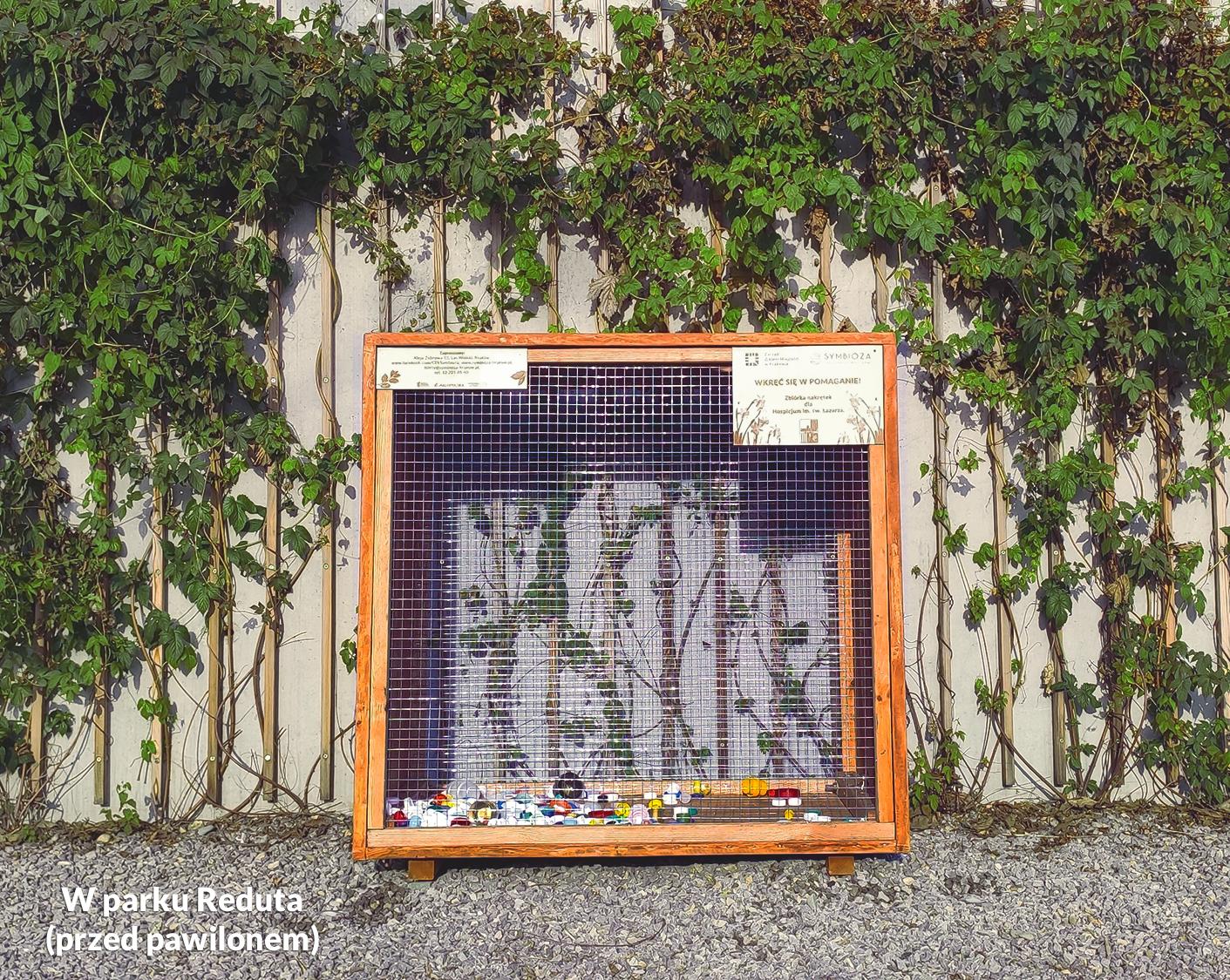 Zdjęcie przedstawiające drewnianą skrzynię na plastikowe nakrętki w parku Reduta - akcja charytatywna CEE Symbioza