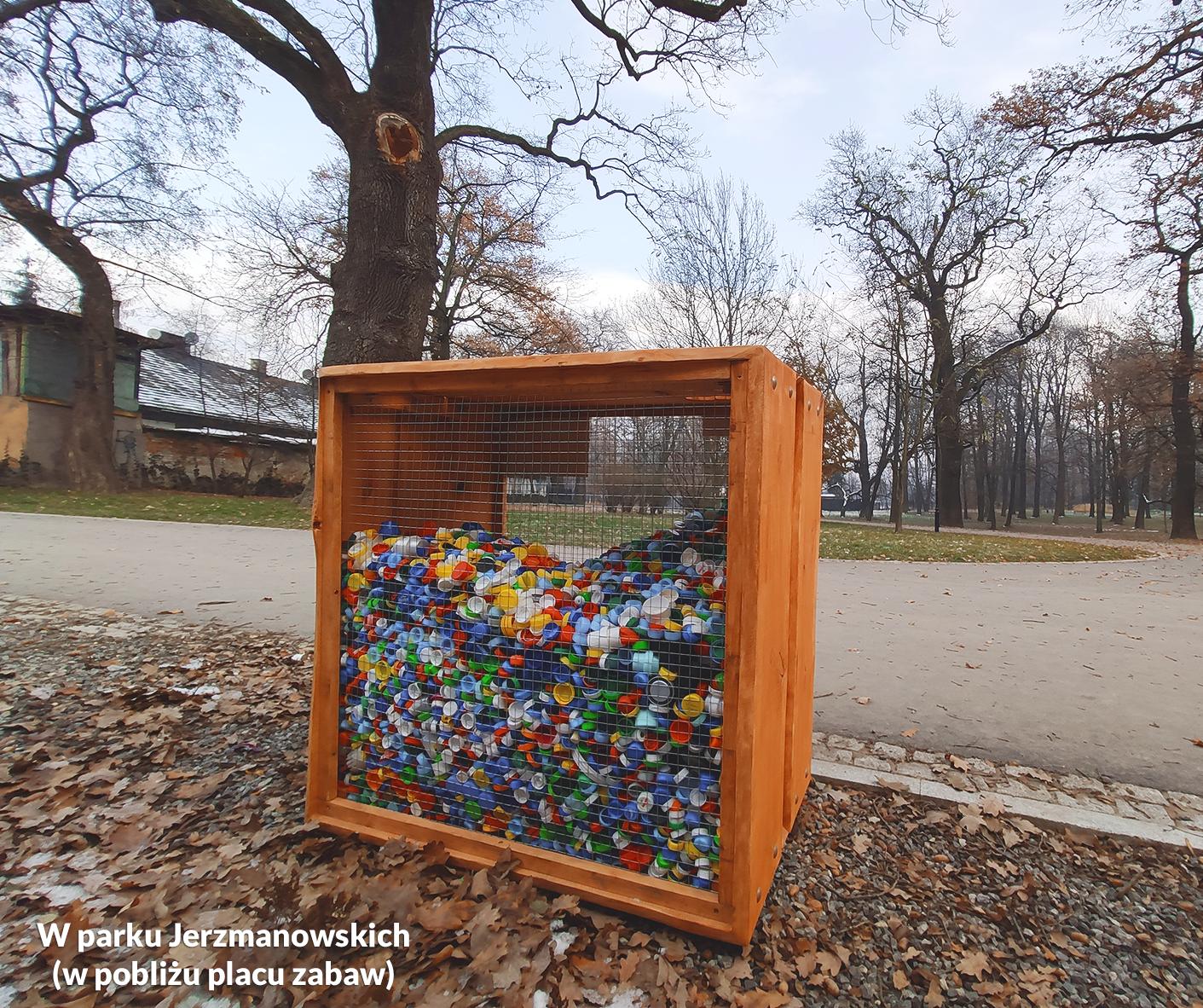 Zdjęcie przedstawiające drewnianą skrzynię na plastikowe nakrętki w parku Jerzmanowskich - akcja charytatywna CEE Symbioza