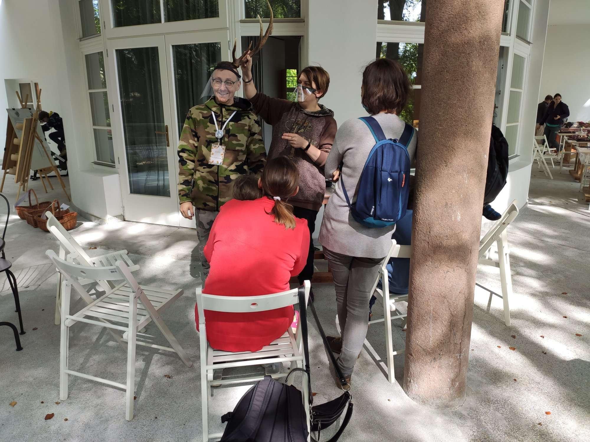 Zdjęcie na tarasie CEE Symbioza przedstawiające dwóch edukatorów w przyłbicach prowadzących warsztaty w lecie - na pierwszym tle uczestnicy zajęć siedzący na białych krzesłach