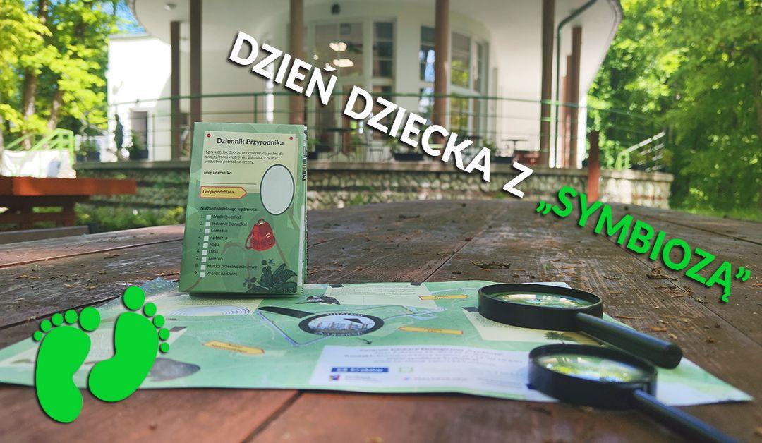 Baner przedstawiający akcję Dzień Dziecka z Symbiozą - w tle gra terenowa na tle budynku Centrum Edukacji Ekologicznej Symbioza