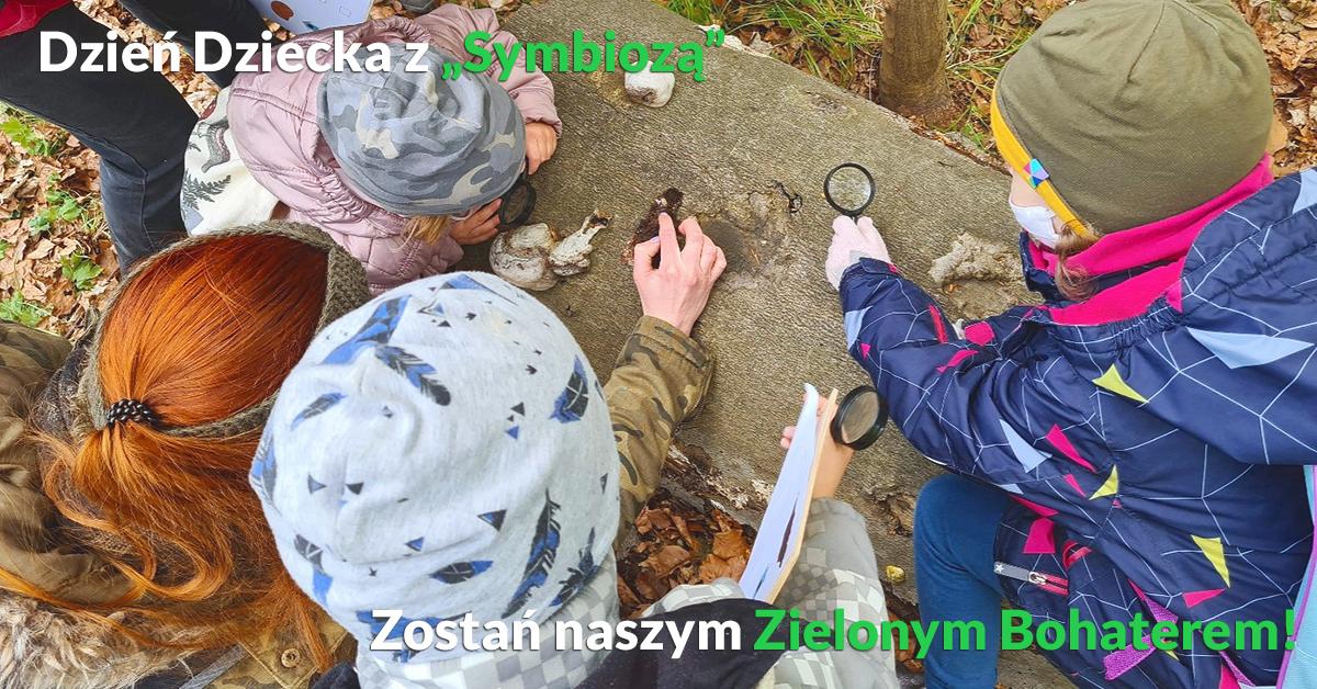 Baner przedstawiający akcję - Zostań Zielonym Bohaterem Symbiozy - w tle dzieci z edukatorem badający martwe drewno lupką